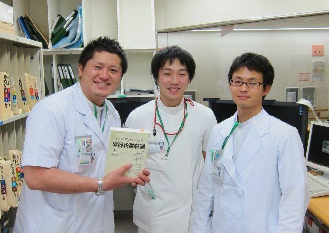 左から山田先生、甲斐先生、佐藤先生。研修開始祝いは脳外科医のバイブル「太田富雄編集 脳神経外科」。